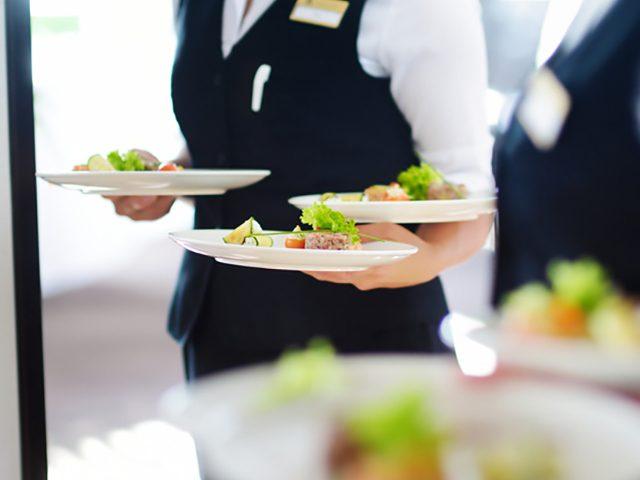 Servicekräfte mit Tellern in der Hand
