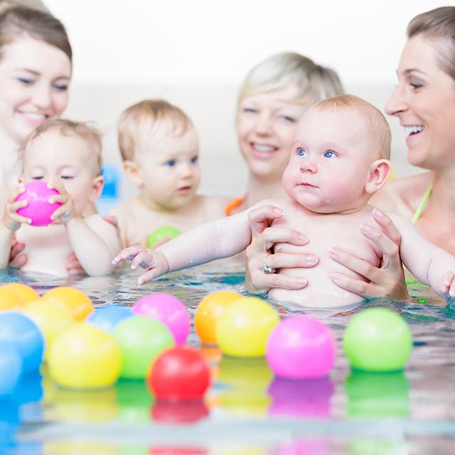 Mütter und Babys spielen mit Bällen im Lehrschwimmbecken
