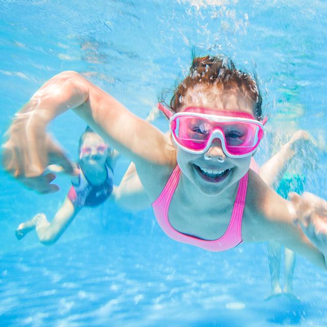 Mädchen tauchen im Schwimmbad und lächeln in die Kamera