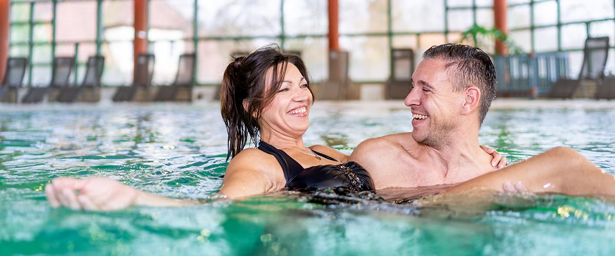 Mann trägt Frau durch das Solewasser