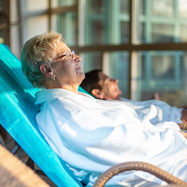 Ältere Dame liegt in der Sonne im Raum des Gradierwerks