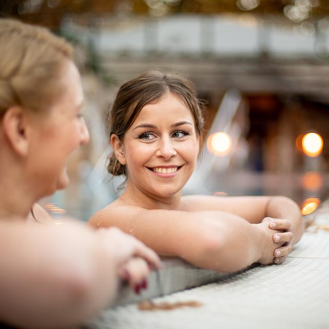 Freundinnen unterhalten sich im Schwimmbecken der Saunaladschaft