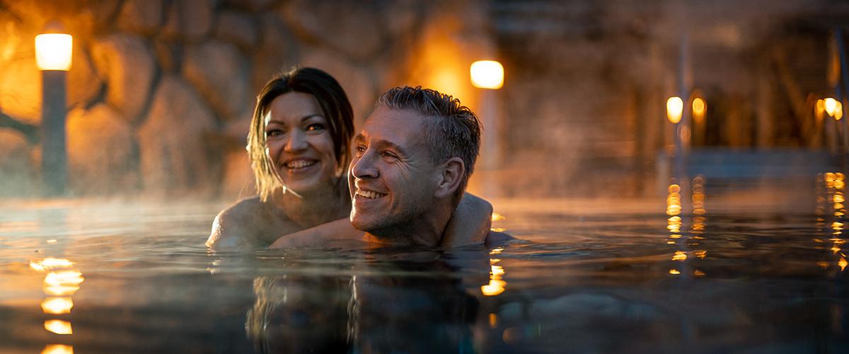 Paar schwimmt in der Dämmerung im Schwimmbecken des Saunagartens