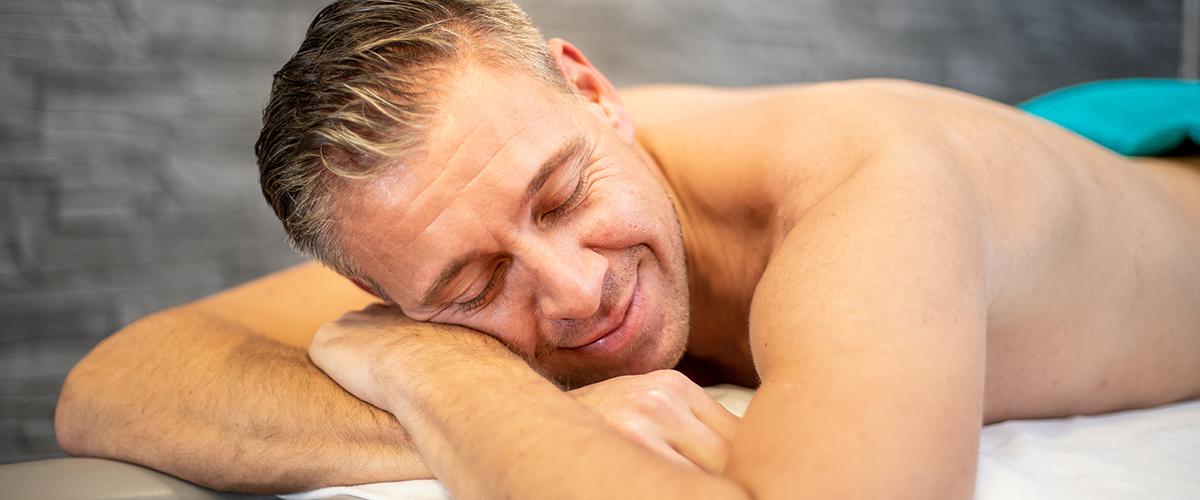 Mann liegt auf der Massagebank