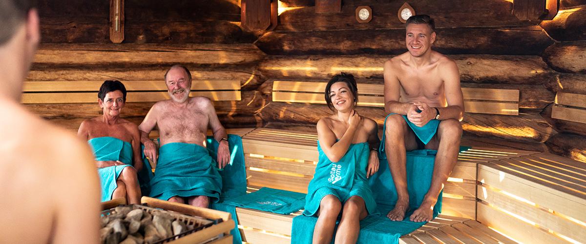 Zwei Paare sitzen in der Kelo-Sauna und genießen den Aufguss