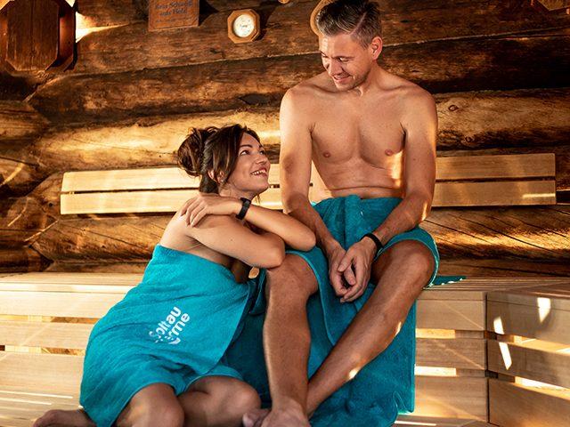 Paar sitzt zusammen in der Kelo-Sauna und unterhalten sich