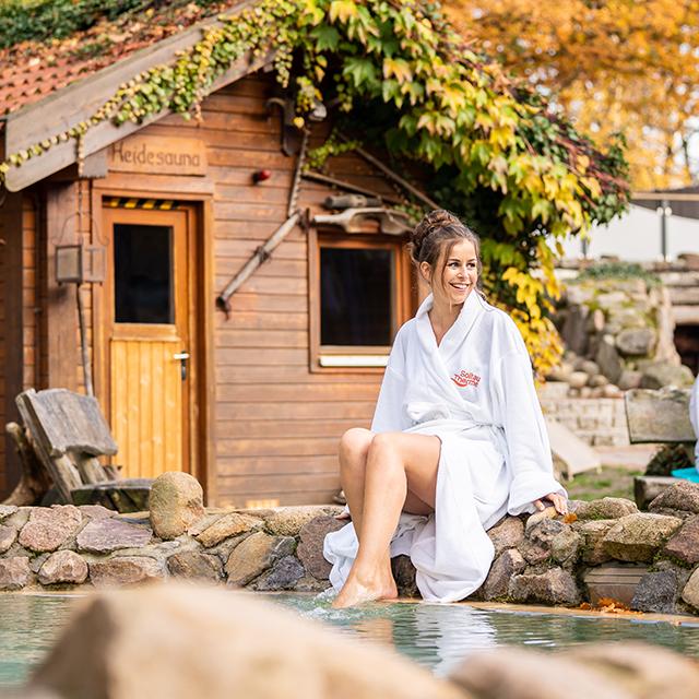 Frau sitzt am Rand des Tauchbeckens im Saunagarten