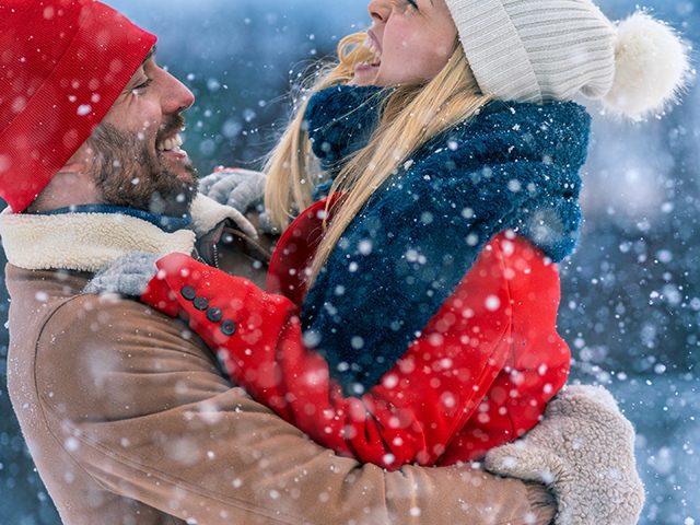 Glückliches Paar umarmt sich im Schnee