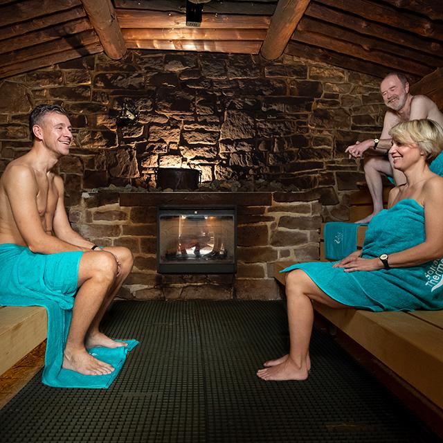 Saunagäste sitzen sich in der Erd-Sauna mit Kamin gegenüber