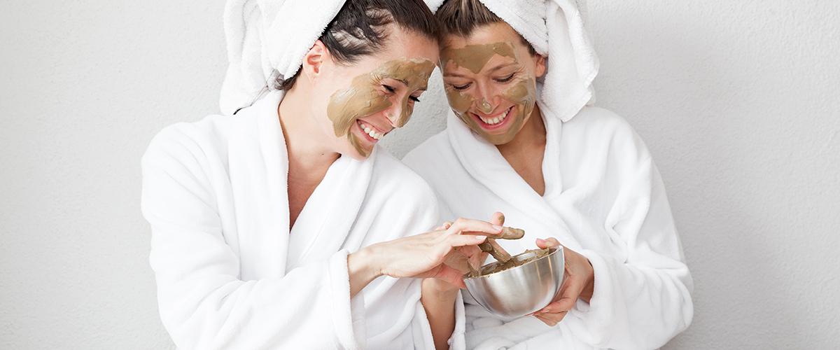 Frauen tragen sich Gesichtsmaske auf