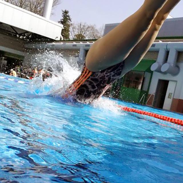 Frau springt ins Schwimmbecken